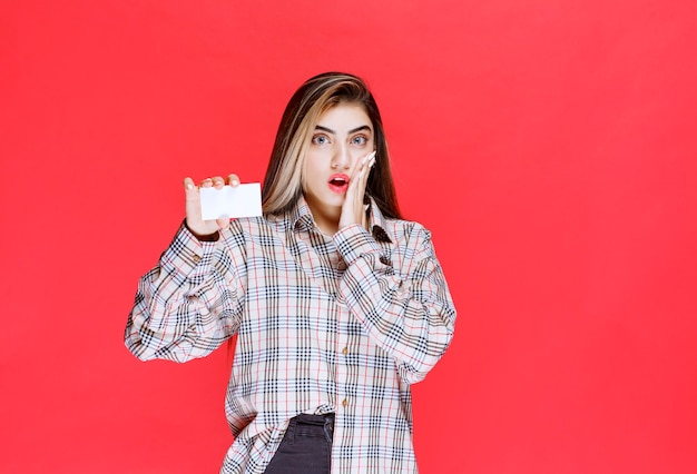 Dziewczyna w kraciastej koszuli trzyma wizytówkę i wygląda na zaskoczoną
