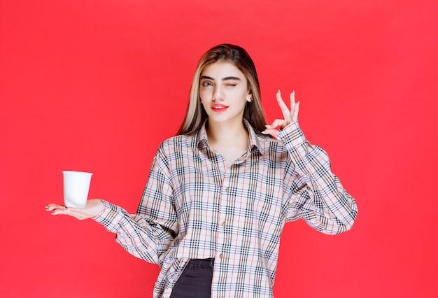 Dziewczyna w kraciastej koszuli trzymająca białą jednorazową filiżankę kawy i delektująca się smakiem
