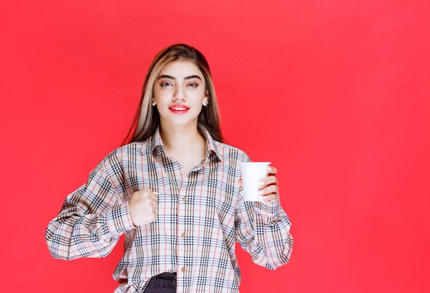 Dziewczyna w kraciastej koszuli trzymająca białą, jednorazową filiżankę kawy i pokazująca swoją moc