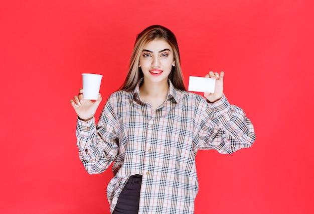 Dziewczyna w kraciastej koszuli trzymająca filiżankę kawy i prezentująca swoją wizytówkę
