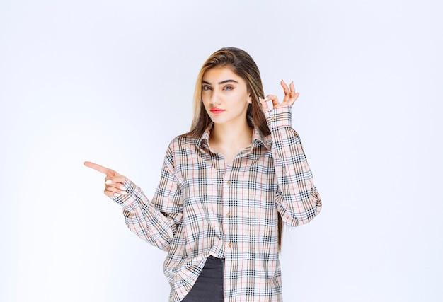 Dziewczyna w kraciastej koszuli wskazująca na kogoś dookoła i pokazująca znak ok ręką