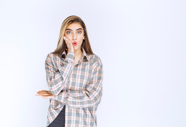 Dziewczyna w kraciastej koszuli wygląda na przestraszoną i przerażoną