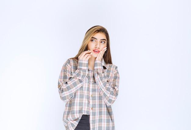 Dziewczyna w kraciastej koszuli wygląda na zamyśloną i niepewną