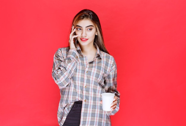 Dziewczyna w kraciastym swetrze przy filiżance drinka podczas rozmowy przez telefon
