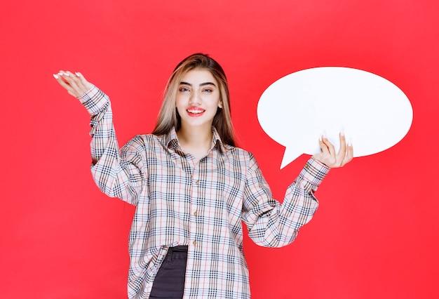 Dziewczyna w kraciastym swetrze trzymająca owalną tablicę z pomysłami i wskazującą na uczestników