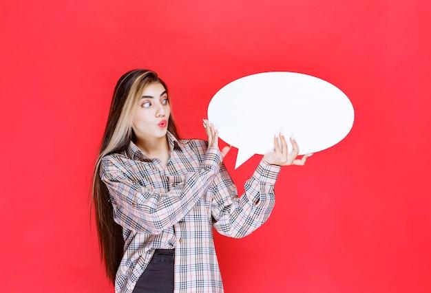 Dziewczyna w kraciastym swetrze trzymająca owalną tablicę z pomysłami wygląda na zdezorientowaną i podekscytowaną