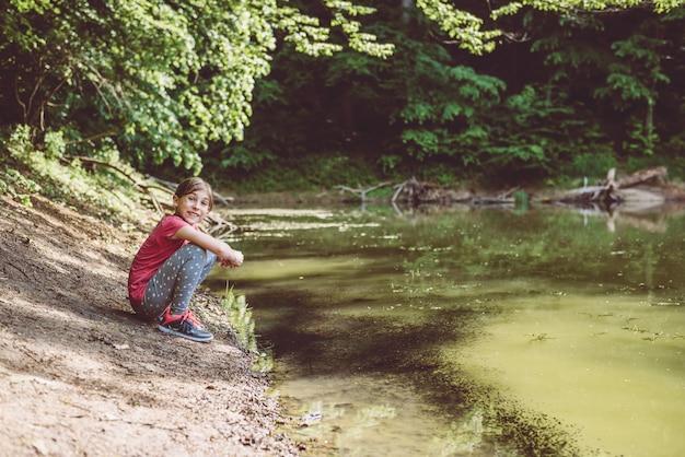 Dziewczyna w kucki nad jeziorem