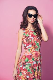 Dziewczyna w kwiecistej sukni i okularów przeciwsłonecznych pozować