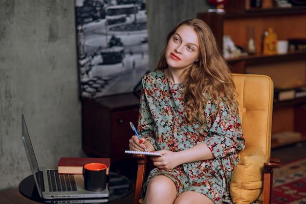 Dziewczyna w kwiecistej sukni siedzi i robi notatki w swoim notatniku.