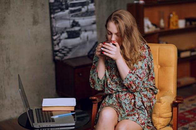 Dziewczyna w kwiecistej sukni siedzi i trzyma brązowy kubek kawy.