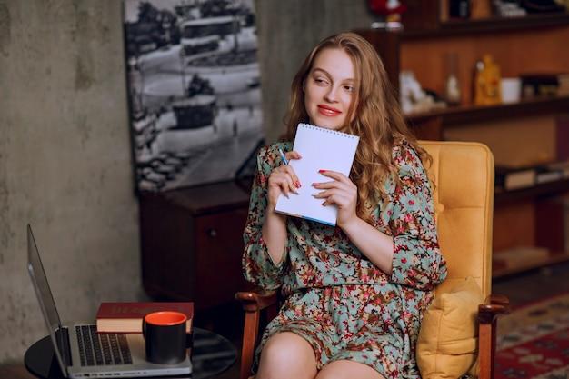 Dziewczyna w kwiecistej sukni siedzi i trzyma książkę.