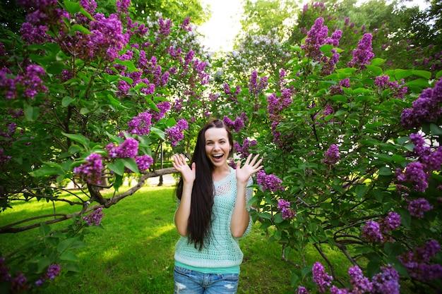 Dziewczyna w kwitnącym ogrodzie. kobieta szczęśliwa w parku.