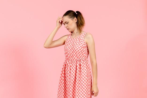 Dziewczyna w ładny jasny strój z wyrażeniem myślenia na różowo