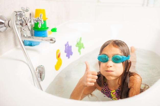 Dziewczyna w łazience nosi okulary do pływania