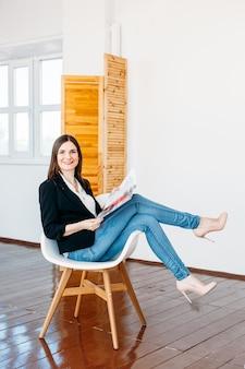 Dziewczyna w lekkiej kurtce dżinsowej siedzi na krześle z magazynem w rękach, moda, czytanie, rozrywka, zawód, wydawca, wolny strzelec, dom