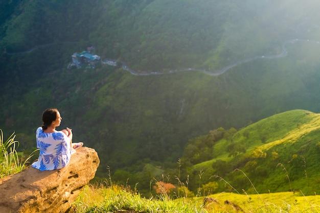 Dziewczyna w lekkiej sukni siedzi na kamieniu na skraju urwiska. widok górski z wysokości.