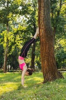 Dziewczyna w lekkim dresie robi joga w parku po południu w lecie