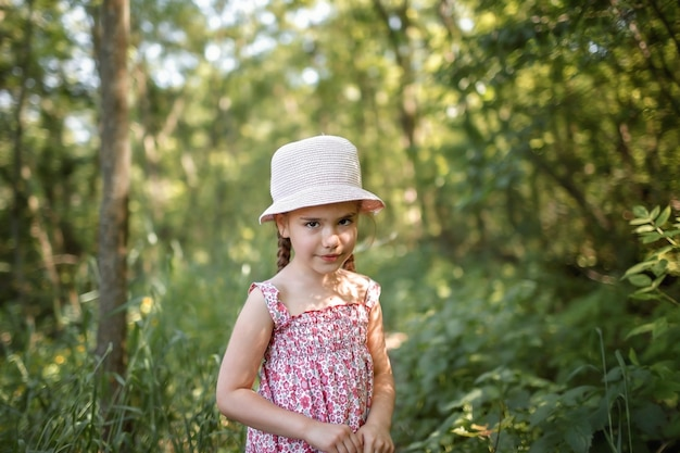 Dziewczyna w letniej lnianej sukience spacerując wśród drzew w lesie i zbierając bukiet dzikich kwiatów