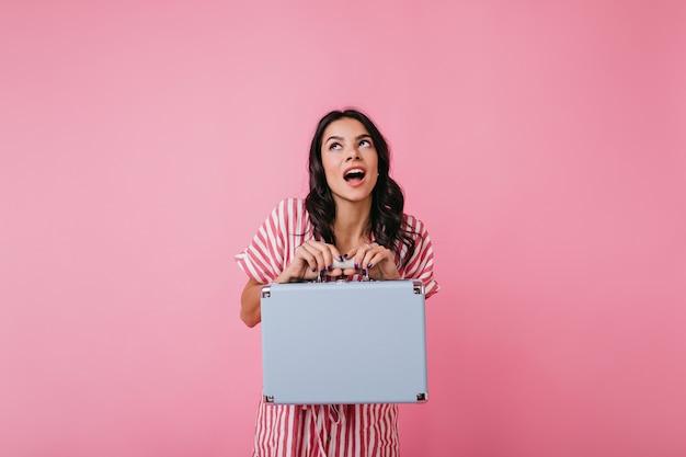 Dziewczyna w letniej sukience, emocjonalnie pozuje z ładną ręczną walizką