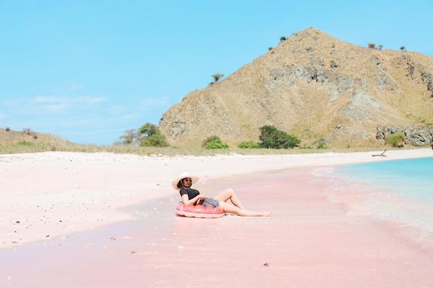 Dziewczyna w letnim kapeluszu relaksuje się na nadmuchiwanej w różowej piaszczystej plaży