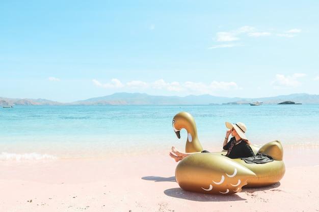 Dziewczyna w letnim kapeluszu siedzi na nadmuchiwanym łabędzie, podziwiając widok na morze w różowej piaszczystej plaży