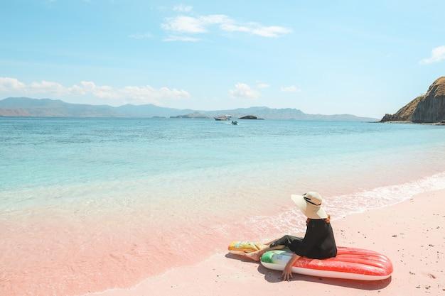 Dziewczyna w letnim kapeluszu siedzi na nadmuchiwanym materacu, podziwiając widok na morze w różowej piaszczystej plaży