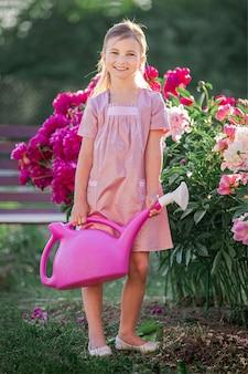 Dziewczyna w lnianej różowej sukience dba o piwonie w słoneczny letni wieczór w ogrodzie, podlewa kwiaty. pięknie się uśmiecha.