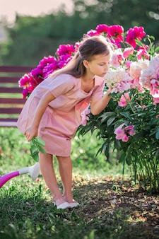 Dziewczyna w lnianej sukience dba o piwonie w lecie w ogrodzie