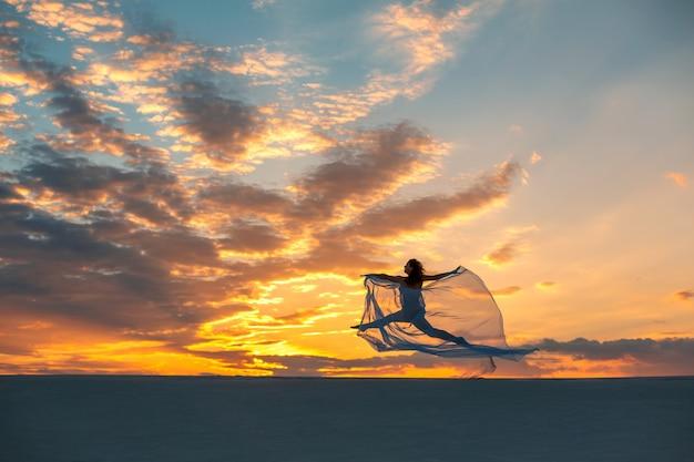 Dziewczyna w locie biała sukienka tańczy i pozuje na piasku pustyni o zachodzie słońca