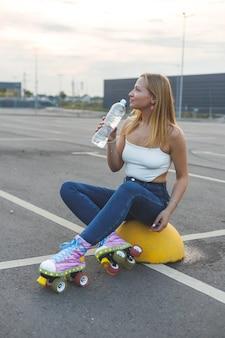 Dziewczyna w łyżworolkach siedzi na parkingu i pije wodę z butelki