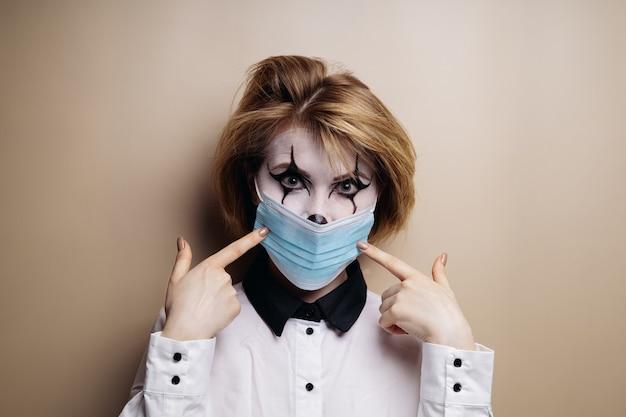 Dziewczyna w makijażu na halloween założyła maskę medyczną i wskazuje ją palcami