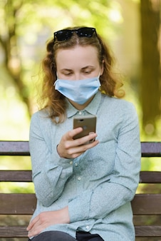 Dziewczyna w masce chirurgicznej sprawdza swój telefon w miejscu publicznym