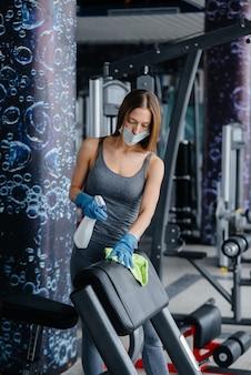 Dziewczyna w masce dezynfekująca sprzęt na siłowni podczas pandemii.