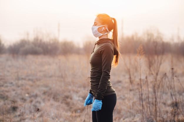 Dziewczyna w masce i niebieskich rękawiczkach podczas kwarantanny wyszła biegać