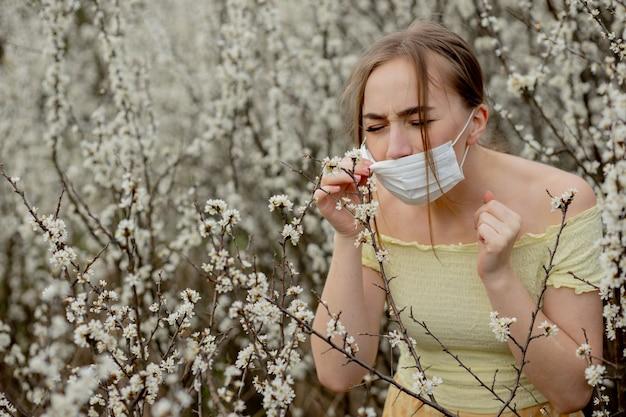 Dziewczyna w masce medycznej. dziewczyna na wiosnę wśród kwitnącego ogrodu. dziewczyna w ochronnej masce medycznej. koncepcja alergii wiosna.