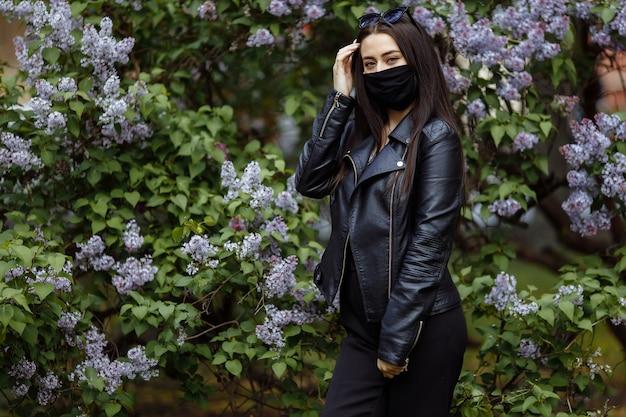 Dziewczyna w masce medycznej nad kwitnącymi bzami. czarna maska. ochrona przed wirusami, grypą. koronawirus ochrona. epidemia koronawirusa. zapach drzewo w ogrodzie wiosenna alergia.