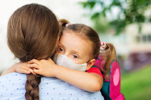 Dziewczyna w masce medycznej przytula matkę przed szkołą koncepcja opieki, edukacji i zdrowia