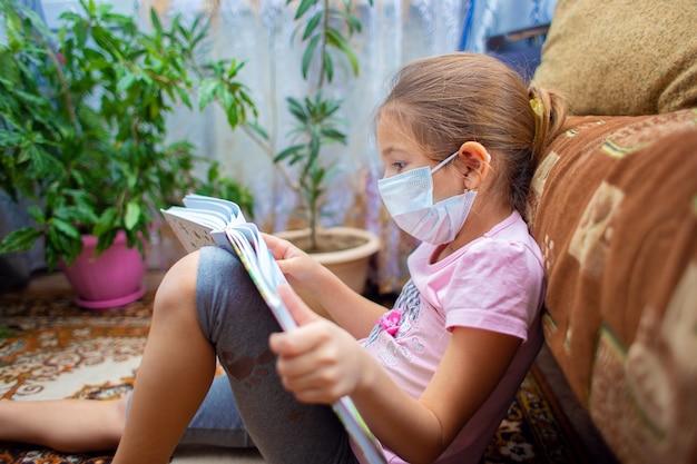 Dziewczyna w masce medycznej siedzi w domu na podłodze i czyta dużą książkę