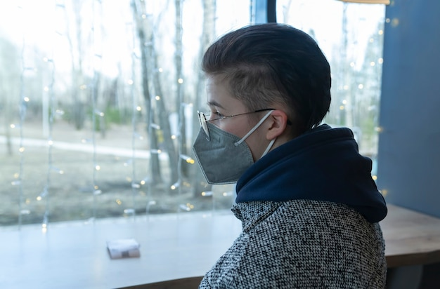 Dziewczyna w masce medycznej siedzi w kawiarni i ze smutkiem wygląda przez okno