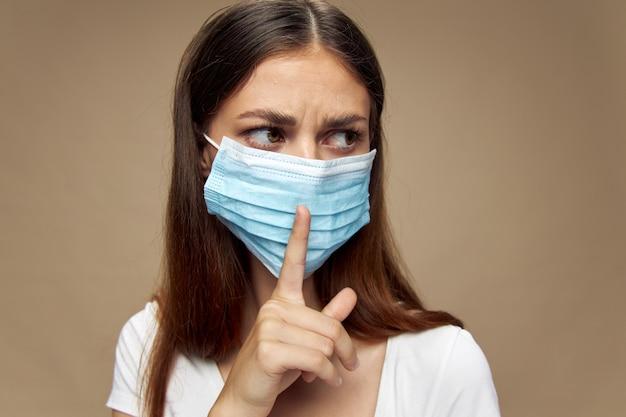 Dziewczyna w masce medycznej trzyma palec przed twarzą i spogląda w bok na beżową przestrzeń