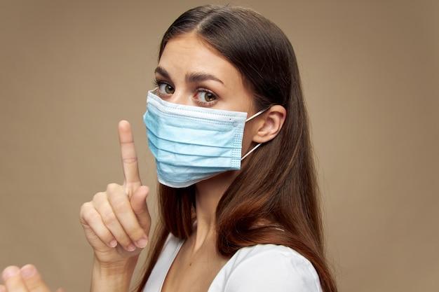 Dziewczyna w masce medycznej trzyma palec wskazujący w pobliżu twarzy opieki zdrowotnej