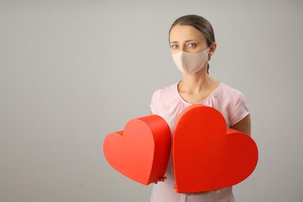 Dziewczyna w masce medycznej trzyma w rękach dwa duże czerwone serca, miejsce na kopię