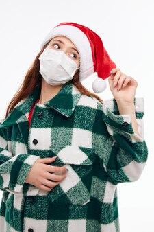 Dziewczyna W Masce Medycznej Ubrania Noworoczne Wyglądają Na Jasnym Tle Strony. Wysokiej Jakości Zdjęcie Premium Zdjęcia