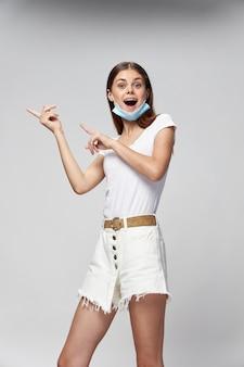 Dziewczyna w masce medycznej w szortach i białej koszulce koronawirusa