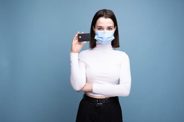 Dziewczyna w masce medycznej z kartą bankową na niebieskiej ścianie.