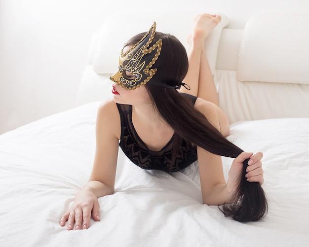 Dziewczyna w masce na białym łóżku