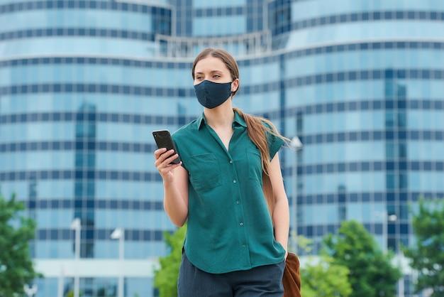 Dziewczyna w masce na twarz trzymająca smartfon wsuwająca dłoń do kieszeni spodni w centrum miasta