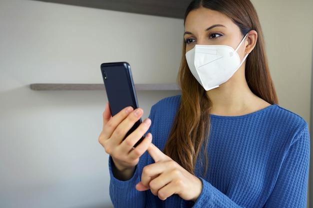 Dziewczyna w masce na twarzy czyta wiadomości w swoim smartfonie w pomieszczeniu