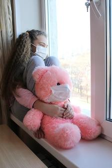 Dziewczyna w masce na twarzy siedzi w domu na parapecie i patrzy przez okno na ulicę. dziewczyna przytula zabawkowego różowego niedźwiedzia w masce.