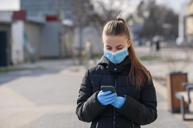 Dziewczyna w masce ochronnej i rękawiczkach za pomocą smartfona na zewnątrz. covid 19. światowa pandemia koronawirusa.